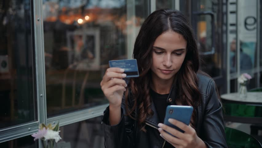 Young woman holding credit card and using laptop computer. Online shopping concept in modern cafe happy brunette girl student tourist on vacation | Shutterstock HD Video #1016828137