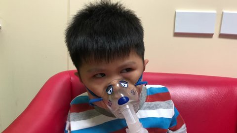 Little boy dose inhalations with a nebulizer mask, Asian people having medical at hospital