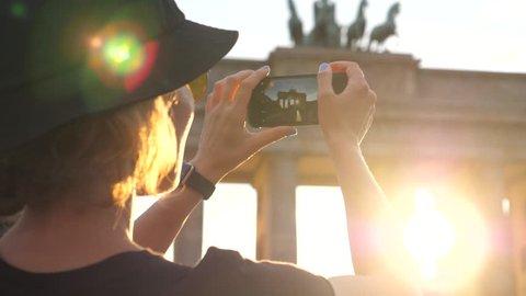Traveler Tourist Woman Taking Photo Of Brandenburg Gate With Smartphone At Sunset