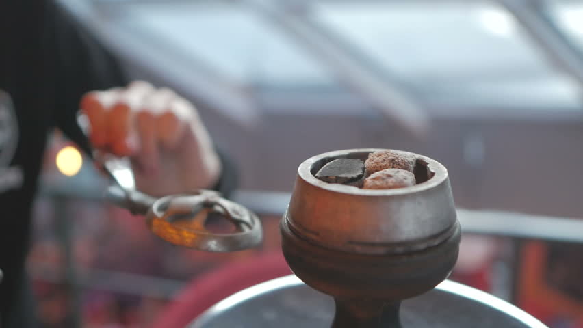 Hookah close-up. A man's hand puts coal in a hookah.
