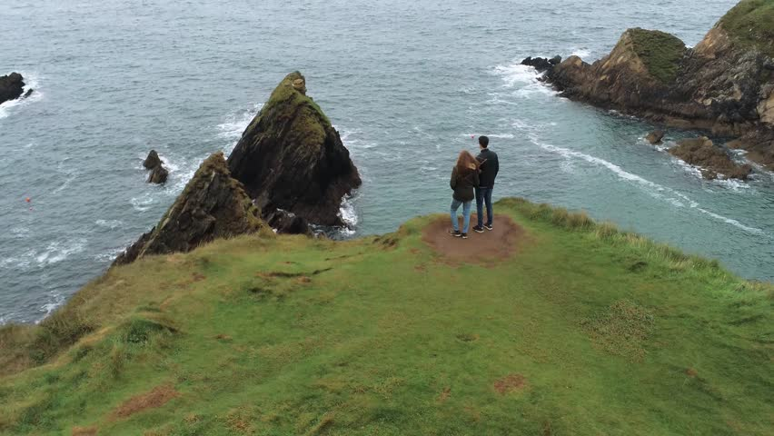 Young couple enjoy the view over Dunquin Pier in Ireland | Shutterstock HD Video #1016875867