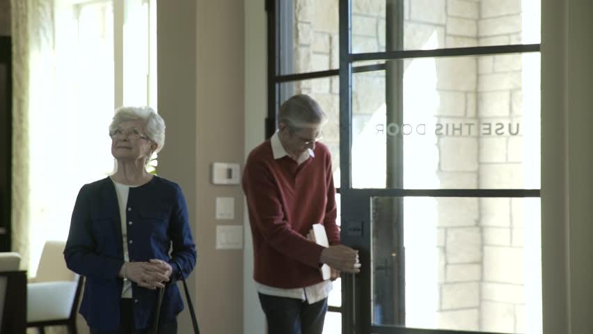 Handheld shot of senior couple visiting financial advisor in office