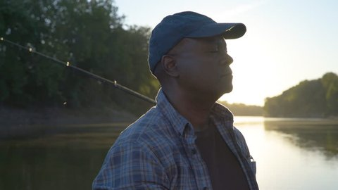 Close-up handheld shot of smiling father and son fishing on lake during sunny day
