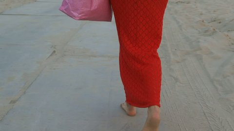 the sexy red-haired woman walks through the desert after shopping. The woman holds a paper bag in her hand for 25 years. long red dress, red oriental turban, large gold earrings.