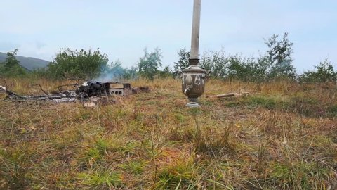 Samovar, a jug with funnel in the middle, and campfire. Summer day in mountains. Still camera