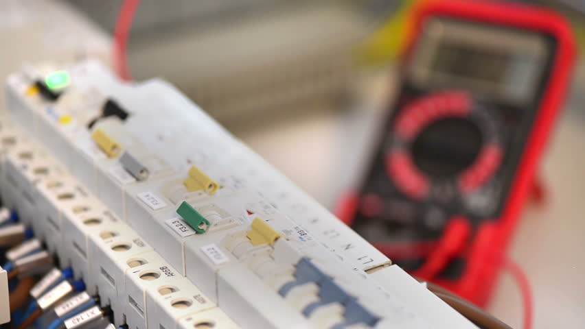 Electrician testing an electric smart panel fuse box, using a multimeter tester