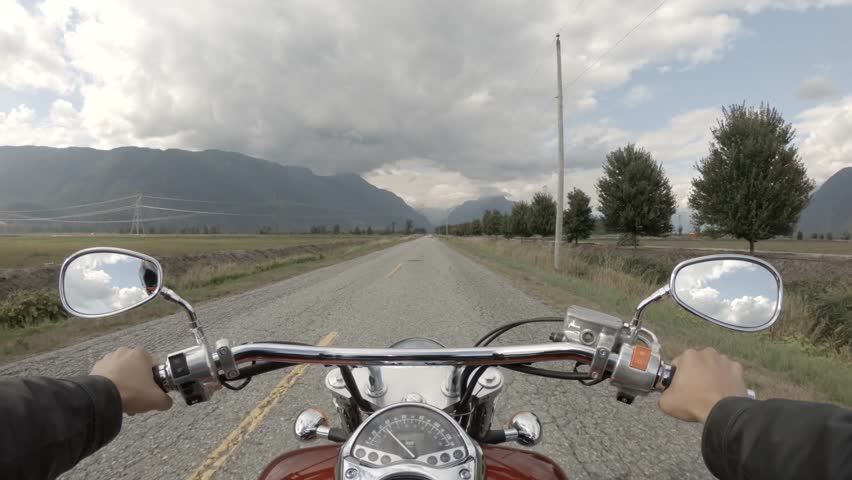 Riding on a motorcycle on a beautiful scenic road surrounded by the Canadian Mountains. Taken in Pitt Meadows, Greater Vancouver, BC, Canada.