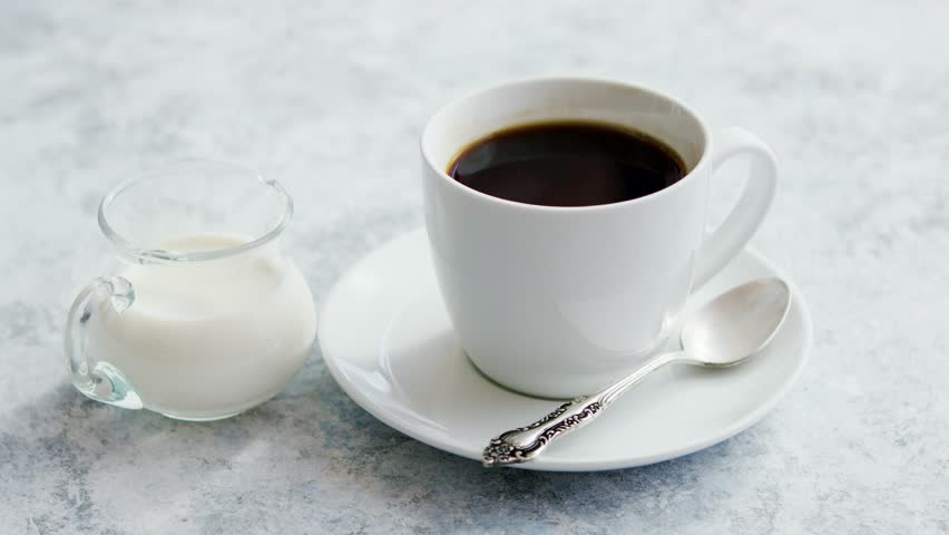 Arrangement Of Small Glass Pitcher With Fresh Milk On Marble Table With  White Cup Of Coffee With Silver Spoon On Saucer