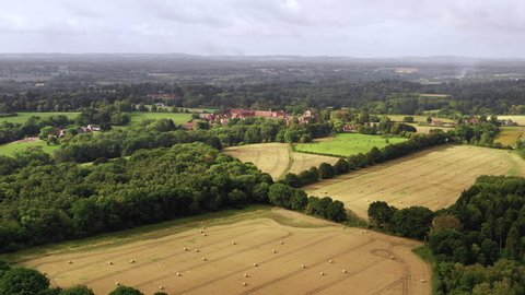 4K aerial forward over harvested fields late summer english countryside