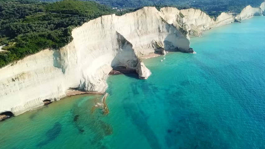 Aerial drone video of iconic white rock steep cliff volcanic bay of Cape Drastis and Peroulades area with tropical deep turquoise clear sea, Corfu island, Ionian, Greece