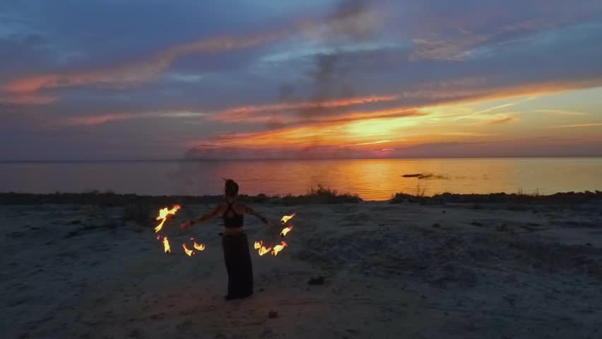 Beautiful woman walks to the river holding burning fire fans #1016994277
