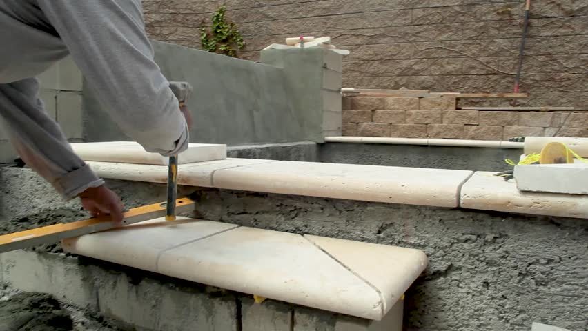 Pool construction worker building and leveling concrete stair with paver entering into spa.