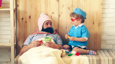A small doctor treats his patient with pills. A little boy in a doctor's suit gives pills to a bearded sick man who lays on a bed under a blanket in a knitted had. Concept of treatment for patients