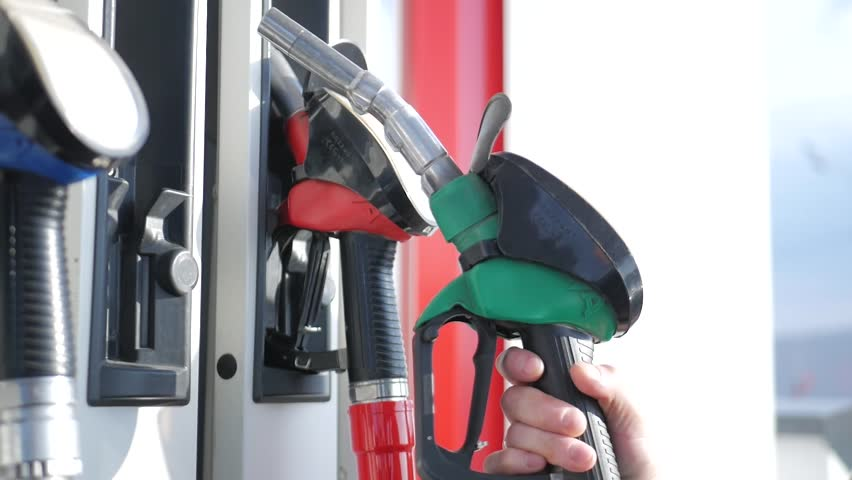 Close up of petroleum gasoline station service - oil refueling and refilling for car transportation concept. Gas station, Fuel pump, Petrol pump filling nozzles.