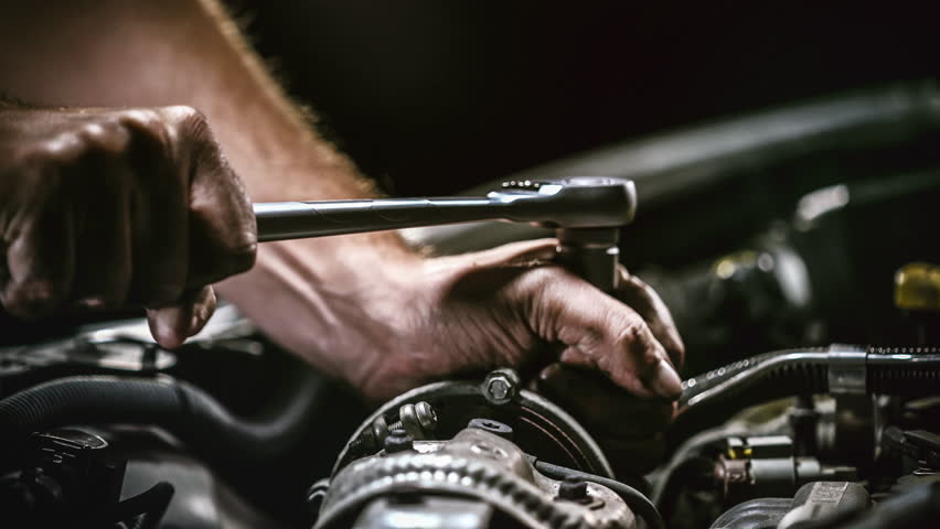 Auto mechanic working on car engine in mechanics garage. Repair service. authentic close-up shot (Shot on RED) | Shutterstock HD Video #1017064897