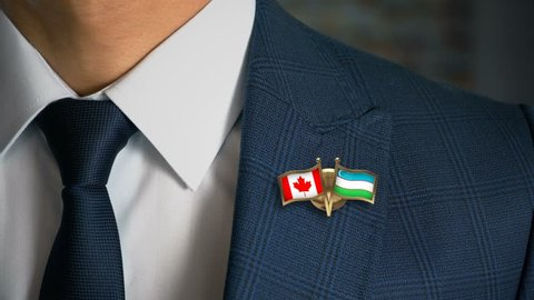Businessman Walking Towards Camera With Friend Country Flags Pin Canada - Uzbekistan