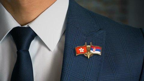 Businessman Walking Towards Camera With Friend Country Flags Pin Hong Kong - Serbia