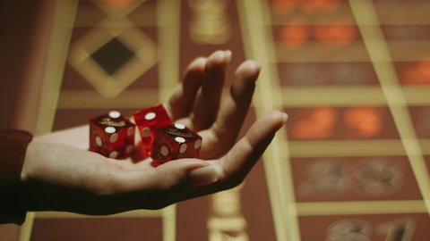 Player hand throwing red dices on gambling table. Entertainment and leisure in vegas casino. Close up woman hand holding three dices. Gambling game in craps at casino. Gambling addiction concept