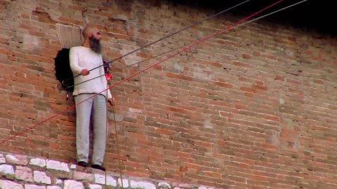 PERUGIA, UMBRIA, ITALY - DECEMBER 9, 2017: Funambulist Andrea Loreni takes the balance pole, preparing to cross Piazza IV Novembre on a tightrope at a 40 metres heigth