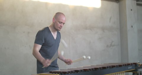 Head and body of a Man Playing the marimba in grey outfit with grey industrial background