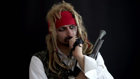 a man in a pirate costume is thinking on a black background. concept idea