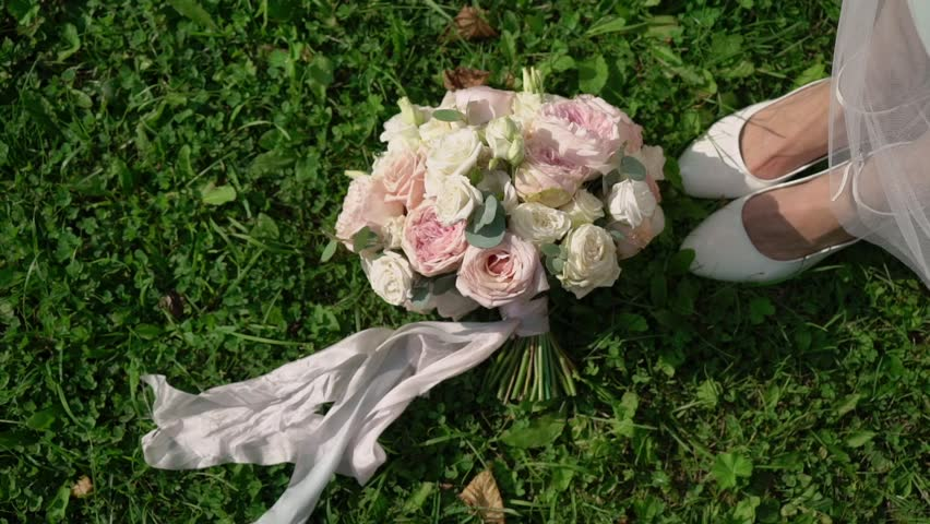 The bride takes her wedding bouquet. In the frame a close-up bouquet on a grass lawn. Woman comes in white bridal shoes and takes it #1017127567