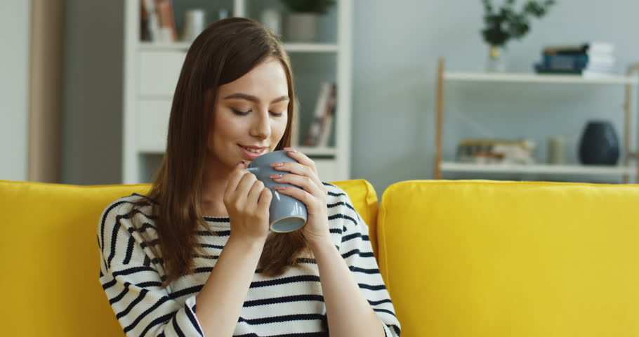 Portrait of the young Caucasian good looking woman drinking coffee or tea and smiling while sitting on the couch at home. | Shutterstock HD Video #1017150757