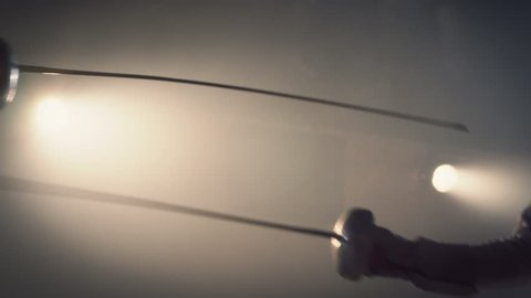 Close up of two swords and fencing athletes duel . Two Professional Fencers Show Masterful Swordsmanship in their Foil Fight. Shot on ARRI ALEXA cinema camera in slow motion .