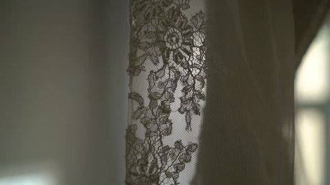 29766be9a4 Luxury wedding dress hanging in bedroom. Silhouette of amazing bride s lace  gown in light.