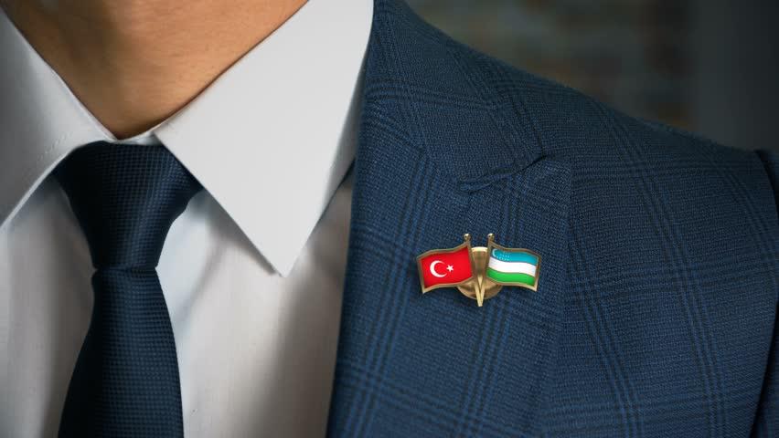 Businessman Walking Towards Camera With Friend Country Flags Pin Turkey - Uzbekistan