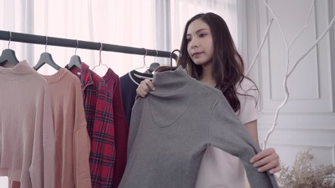 Home wardrobe or clothing shop changing room. Mixed race Asian and Caucasian young woman choosing her fashion outfit clothes in closet at home or store. Girl think what to wear sweater.