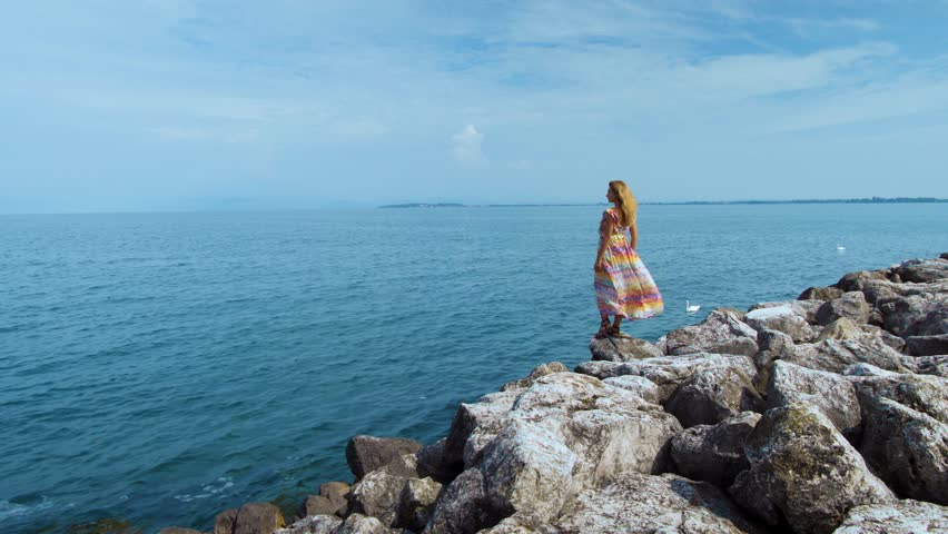 girl in a beautiful dress on stones looking at the ocean #1017212107
