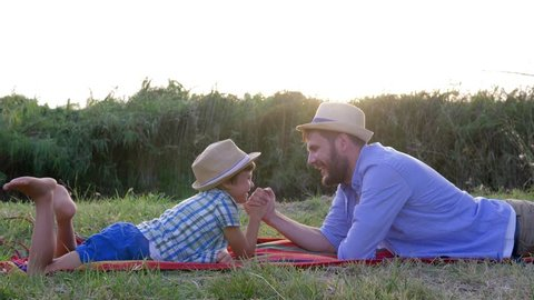 loving father and kid play together in arm wrestling lying on the plaid during weekend leisure outdoors
