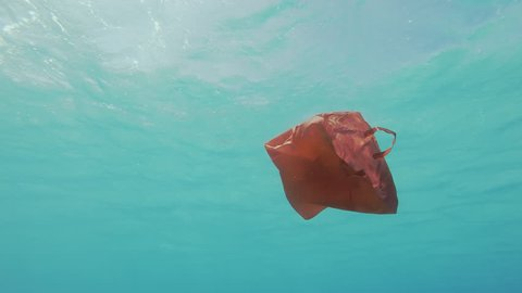 Plastic Pollution. Underwater Shot. Red Plastic Shopping Bag Floating Underwater In The Mediterrenean Sea