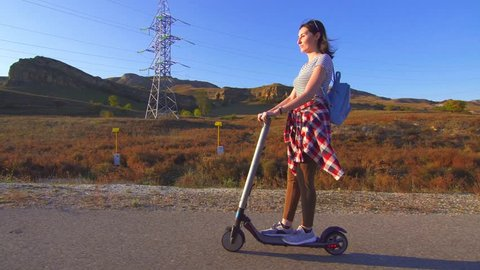 Young girl rides an electric scooter on the road,sun
