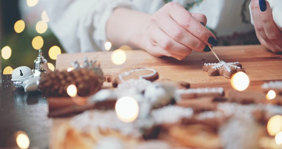 Woman Decorating Baked Gingerbread Christmas Cookies. 4K SLOW MOTION.  Female hands frosting and icing fresh holiday bakery. Festive food, family, Christmas and New Year traditions concept. | Shutterstock HD Video #1017270187
