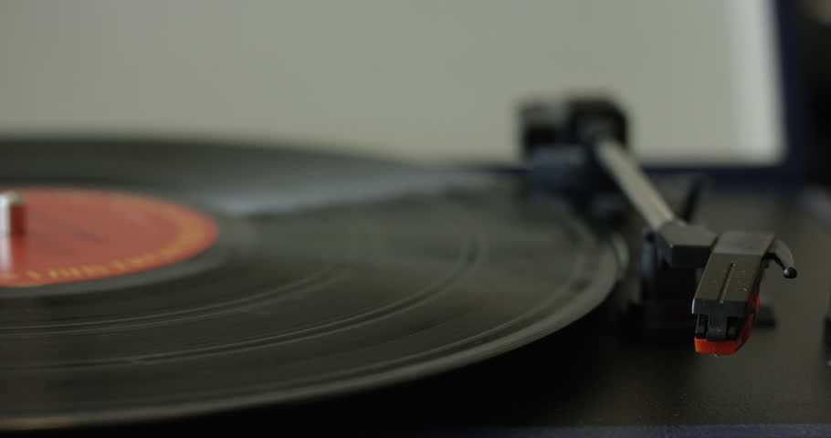 Womans hand places needle onto vinyl record carefully - close up