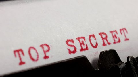 Typing TOP SECRET in red ink on an old mechanical typewriter.