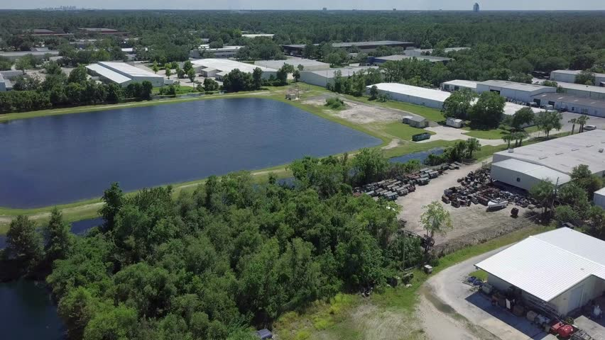 Aerial flyover drone footage of man made retention pond with light industrial buildings in background landscape.