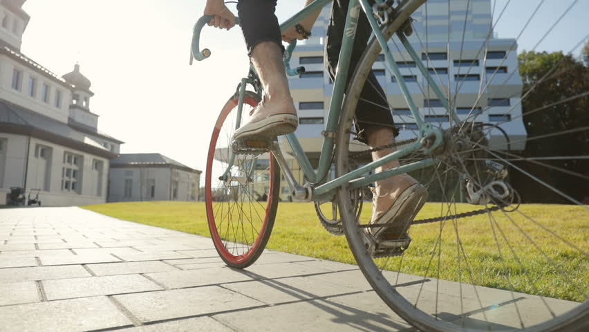 Man in light brown trainers going cycling near huge university facilities, outdoor low angle shot on lovely monday morning | Shutterstock HD Video #1017292597