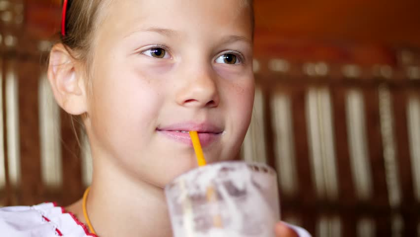 Happy smiling teen girl child drinks a milkshake in cafe. she is dressed in Ukrainian national clothes, embroidery, vishivanka   Shutterstock HD Video #1017297667