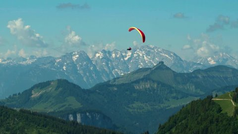 WS TS Paraglider flying above mountains, Zwolferhorn Mountain / St. Gilgen, Salzburg, Austria