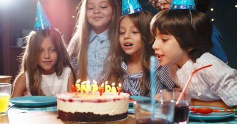 Children celebrating birthday party, blowing out the candles on birthday cake. Group of kids having fun on birthday party - happy childhood concept 4k