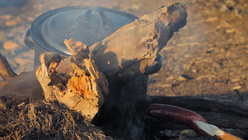 Yukon river, Yukon Territory, Alaska. Night camp of a canoe expedition to Alaska. Cooking pot being heated in a camp fire while sausage cooks on a stick.