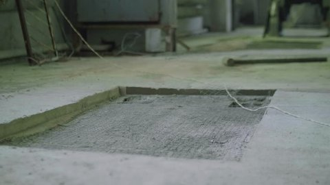 Cavity in concrete floor workshop. Blur view of caucasian man picking up sledge hammer