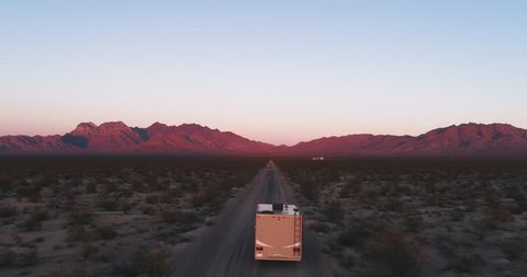 AERIAL - The camera follows an RV that is being lit by the last bit of sun during sunset while driving towards some mountains in the desert