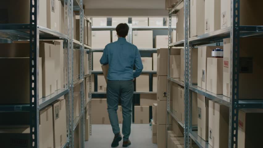 Worker Carrying Cardboard Box Walks Through Warehouse Storeroom with Rows of Shelves Full Cardboard Boxes, Parcels, Packages Ready For Shipment. Shot on RED EPIC-W 8K Helium Cinema Camera. | Shutterstock HD Video #1017422677
