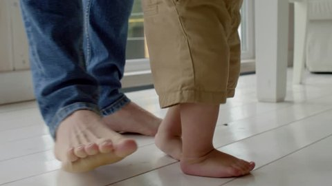 Close-up tracking shot of feet of little baby boy walking barefoot with help of father in home while making first steps
