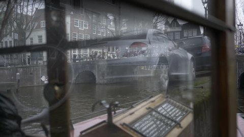 Turistic boat in old-fashioned style parking near embankment. Veew through glass of wheelhouse on the bridge with bicycle and traditional holland building. Amsterdam, Netherlands