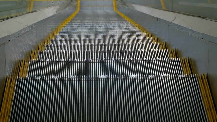 A close-up of the steps of the escalator moving down. A view from the eyes. Shooting with hands without a tripod. Smooth breathing of the operator. | Shutterstock HD Video #1017474277